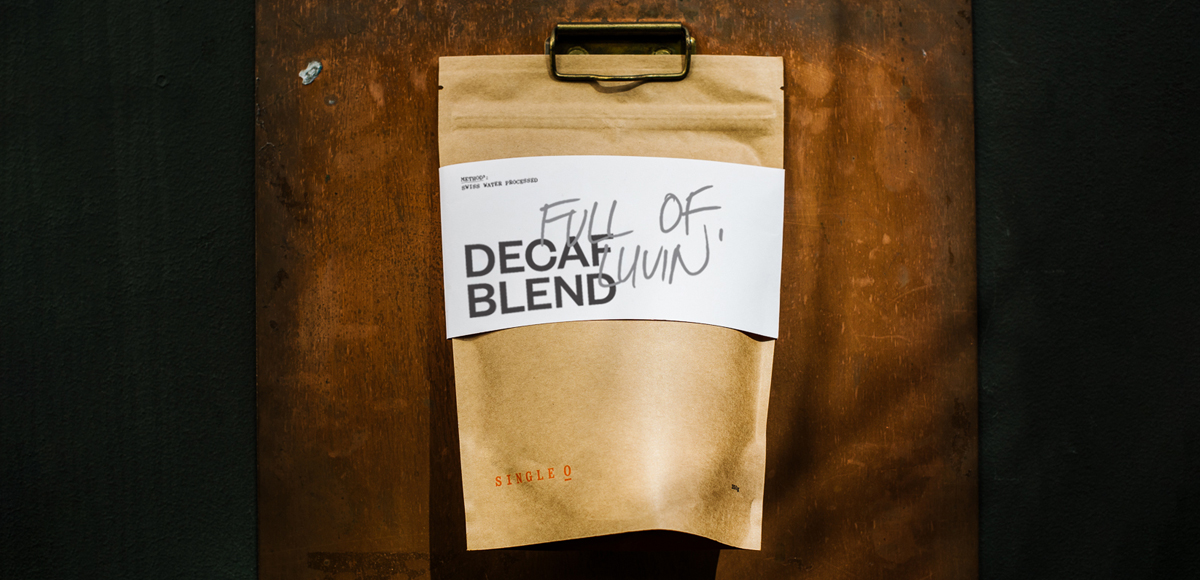 A bag of Single O's Decaf blend hanging from a rusted clip on a wall