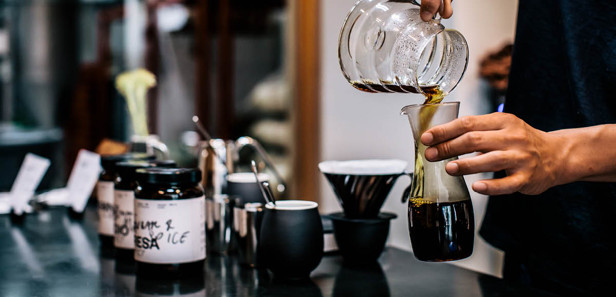 Filter coffee being poured into cup at tasting bar
